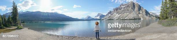 Panoramic of young woman contemplating nature at mountain lake
