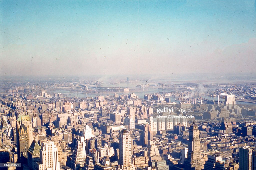 Panoramic view facing northeast of the Lenox Hill neighborhood of upper Manhattan, the East River, northwest Queens, and the southern tip of the Bronx, 1957. The Triborough Bridge, Hells Gate Bridge, and Wards Island Bridge are visible in the background at center, with Wards-Randall's Island beneath them. At right is the northern tip of Welfare Island (Roosevelt Island) visible just below the promontory at Hallet's Point, Astoria, Queens. At right center is New York-Presbyterian Hospital/Weill Cornell Medical Center on 68th Street by the East River. Moving west, the white brick Manhattan House apartment complex takes up the entire block from 2nd to 3rd Avenue, between 65th and 66th Streets. In the foreground from left to right are the tops of the Sherry-Netherland Hotel, the Savoy-Plaza Hotel, the Squibb Building, the Fuller Building, and the Ritz Tower at Park and 57th Street. (Photo by Morse Collection/Gado/Getty Images).