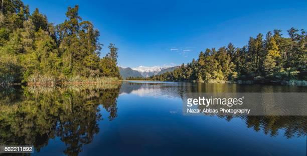 Panoramic view Mt Tasman and Mt Cook reflecting in Lake Matheson.