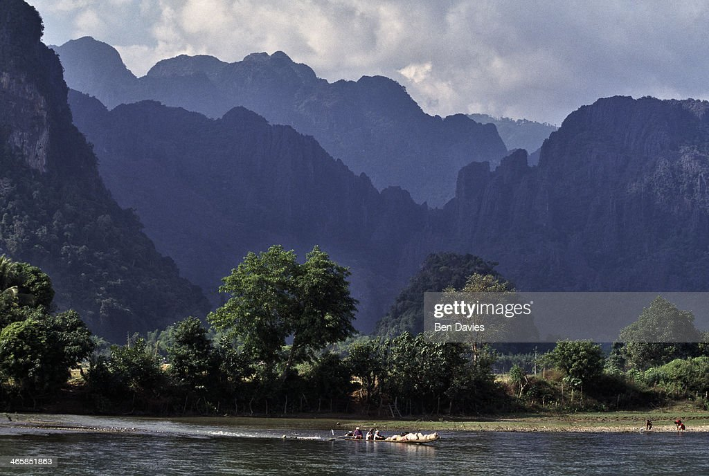 Panoramic view of a boat crossing over the river at Vang Vieng a picturesque town surrounded by spectacular limestone cliffs and hills Easily reached...