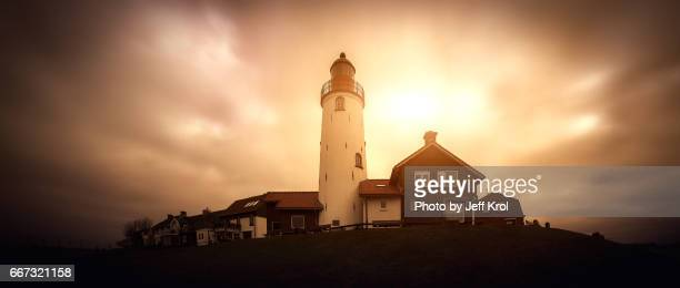 Panoramic view of a lighthouse on a hill with houses, windy sky with sun coming through the clouds.