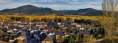 High resolution panoramic view of San Miguel de la Duenas, a charming village in rural Spain, with fall colors and mountains background; high angle view