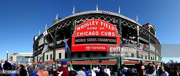 Panoramic view of Cubs fans crowding under the marquee at Wrigley Field home of the Chicago Cubs to celebrate the Cubs' world series win against the...
