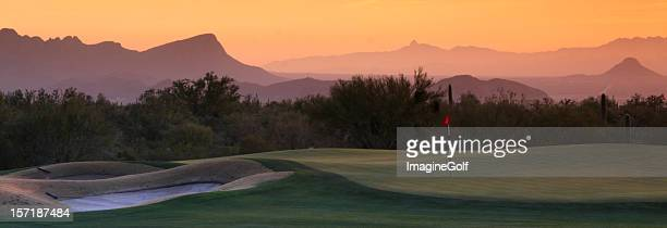 Panoramic view of desert golf course under hazy orange sky.