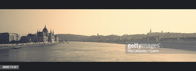 Panoramic View Of Hungarian Parliament Building By Danube River Against Sky