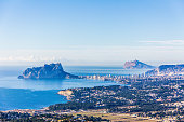 Panoramic view of Ifach Rock Natural Park or 'Penon de Ifach' and Calpe city in Spain. View from Cumbre del Sol mountain, also known as 'Puig Llorenca'
