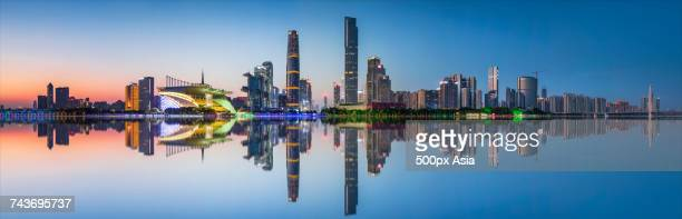 Panoramic view of illuminated modern skyscrapers reflected in Pearl River, Guangzhou, Guangdong, China