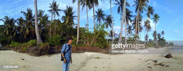 Panoramic View Of Man Looking Away While Standing Against Palm Trees At Beach