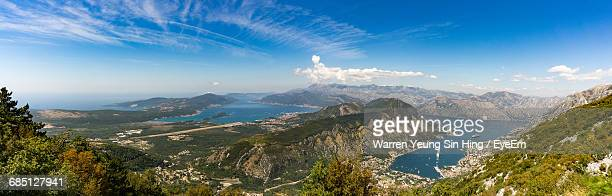 Panoramic View Of Mountains By Sea Against Blue Sky