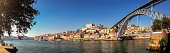 Panoramic view of colorful Ribeira neighborhood in Porto, Portugal and famous bridge Luis I over Douro river, in Portugal