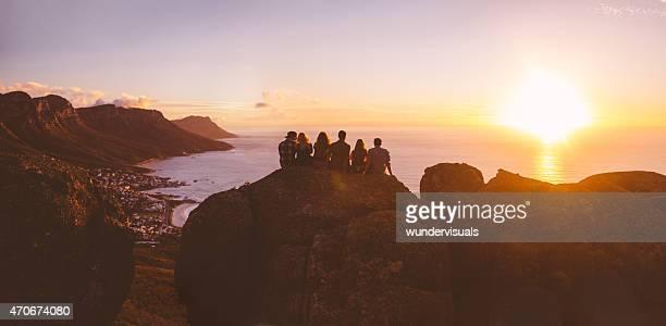 Vue panoramique de silhouettes hipster en regardant le coucher de soleil sur la mer