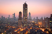 Panoramic view of south central Mumbai - the financial capital of India - at golden hour showing vast contrast in the living conditions of people with dwellings of lower middle class in foreground and