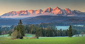 Panoramic view of Tatra mounains.Tatra mountains in the morning. Beautiful green valley at snowy mountains foothills. Picturesgue morning landscape.