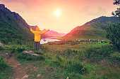 Panoramic view of the fjord. Twilight time with an amazing orange sky. The young man with hands in the air standing on a cliff of rock and gazing sunset. Beautiful mountain landscape at sunset.