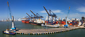 Panoramic view of a port activity with cargo ships, cranes and containers at the pier of the Port Of Cartagena, Colombia.