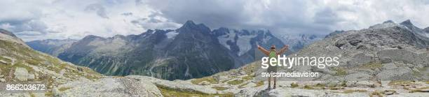 Panoramic view of Young man enjoying freedom in nature, arms outstretched