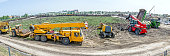 Panorama is showing the group of various machinery landscape transform. Yellow road roller with spikes, crane, cherry picker, telescopic forklift and dumper truck are parked in front of building site.