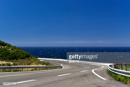 Panoramic winding road that goes along a body of water