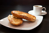 French bread toasted with butter on the plate with coffee. Pao na chapa traditional brazilian breakfast. Selective focus.