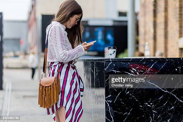 Paola Alberdi wearing a white Kindred blouse a red blue white striped skirt from Finders Keepers a brown Chloe bag outside C Meo Collective at...