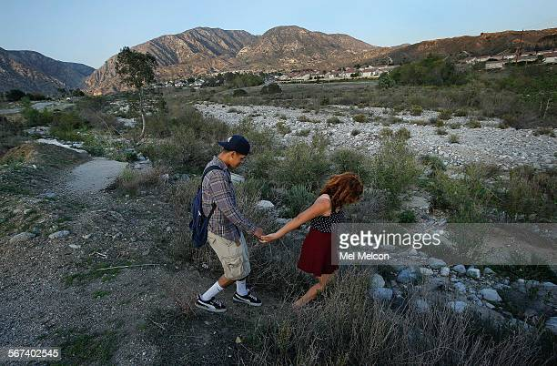 Paola Hernandez left and friend Anthony Perez walk along the Pacoima Wash in Sylmar with the San Gabriel mountains in the backdrop on March 21 2014...