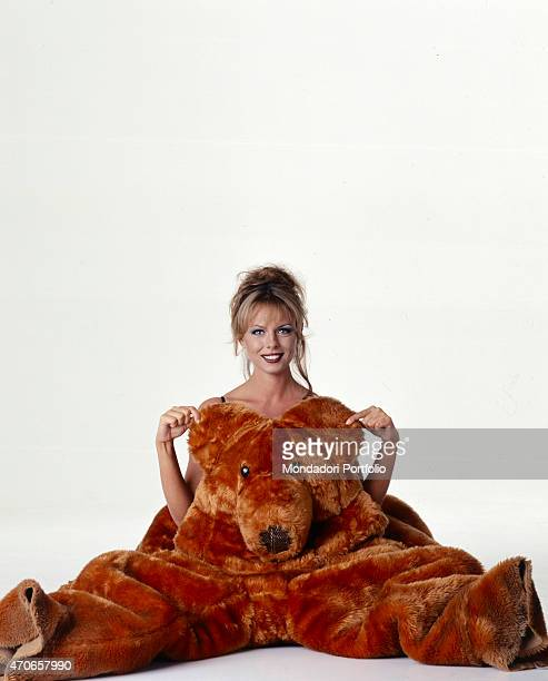 'Paola Perego formerly a model poses into a white photo studio seated on the ground and wearing a big bear costume Perego starting from this season...