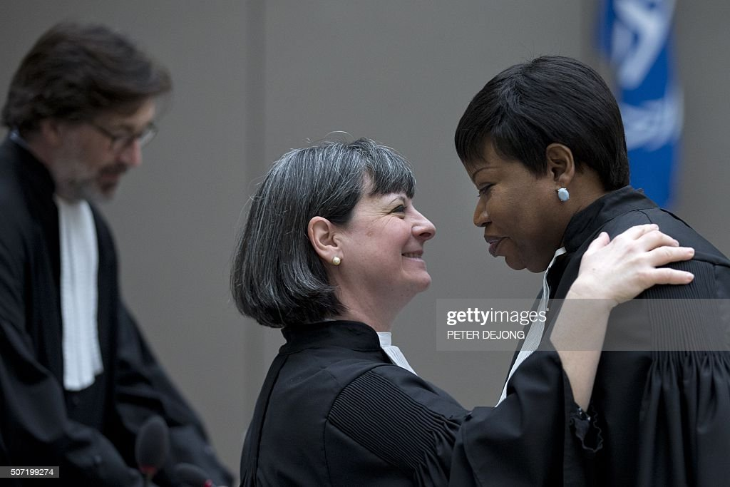 Paolina Massidda, legal representative of the victims (C) greets prosecutor <a gi-track='captionPersonalityLinkClicked' href=/galleries/search?phrase=Fatou+Bensouda&family=editorial&specificpeople=802492 ng-click='$event.stopPropagation()'>Fatou Bensouda</a> (L) as they wait for the start Ivory Coast president Laurent Gbagbo and former minister Charles Ble Goude trial at the International Criminal Court in The Hague on January 28, 2016. The high-profile trial of former Ivorian president Laurent Gbagbo opened on January 28, 2016 five years after post-election violence wracked his nation, with supporters and foes aiming to shed light on the turmoil that left 3,000 dead. / AFP / POOL / Peter Dejong / Netherlands OUT