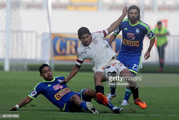 Paolo de la Haza of Sporting Cristal struggles for the ball with Edison Flores of Universitario during a match between Universitario and Sporting...