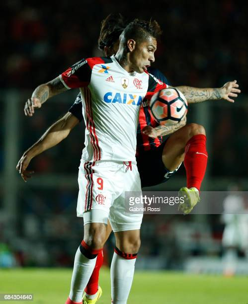 Paolo Guerrero of Flamengo and Marcos Angeleri of San Lorenzo fight for the ball during a group stage match between San Lorenzo and Flamengo as part...