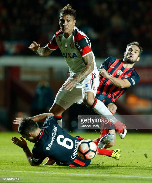 Paolo Guerrero of Flamengo fights for the ball with Matias Caruzzo and Fernando Belluschi of San Lorenzo during a group stage match between San...