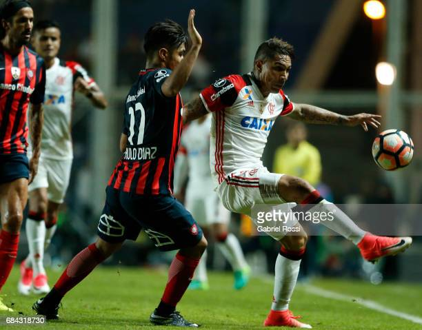 Paolo Guerrero of Flamengo fights for the ball with Paulo Diaz of San Lorenzo during a group stage match between San Lorenzo and Flamengo as part of...