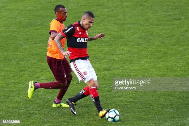 Paolo Guerrero of Flamengo struggles for the ball with Eduardo Henrique of Atletico PR during a match between Flamengo and Atletico PR as part of...