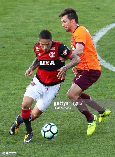 Paolo Guerrero of Flamengo struggles for the ball with Paulo Andre of Atletico PR during a match between Flamengo and Atletico PR as part of...