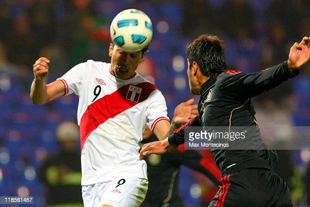 Paolo Guerrero of Peru battles for the ball against Néstor Araujo of Mexico during a match as part of group C of 2011 Copa America at Malvinas...