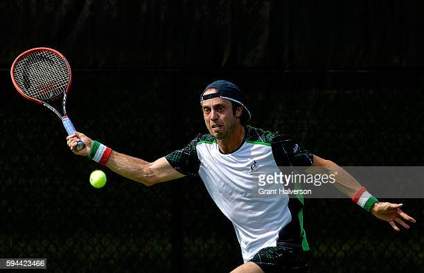 Paolo Lorenzi of Italy returns a shot to Bjorn Fratangelo of the Unites States during the WinstonSalem Open at Wake Forest University on August 23...
