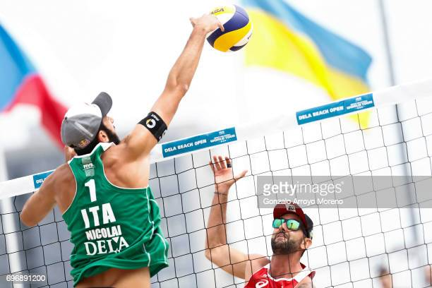 Paolo Nicolai from Italy sends the ball against Clemmens Doppler from Austria during their quarter final match during the FIVB Beach Volleyball World...