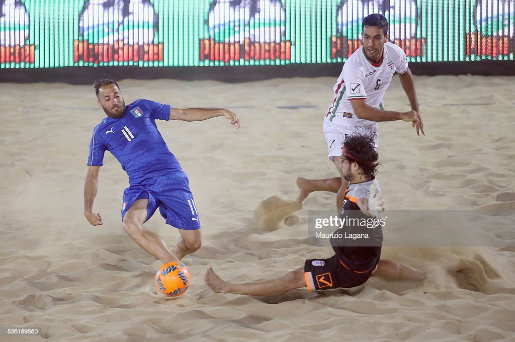 Paolo Palmacci of Italy competes for the ball with Hoseini of Iran during the beach soccer international frienldy between Italy and Iran on May 31, 2016 in Catania, Italy.