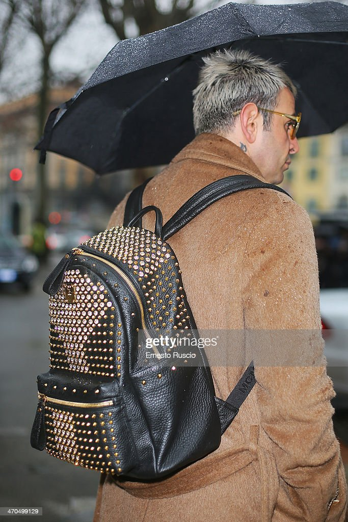 Paolo Sfarra wears Versace trousers, shoes and MCM bag and Margiela Coat on day 1 of Milan Fashion Week Womenswear Autumn/Winter 2014 on February 19, 2014 in Milan, Italy.