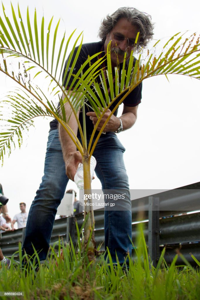 Paolo Simoncelli father of Marco Simoncelli of Italy waters a palm tree planted in memory of Marco Simoncelli during the 'Track walk to Turn 11 for SIC ' ahead of the MotoGP of Malaysia at Sepang Circuit on October 26, 2017 in Kuala Lumpur, Malaysia.