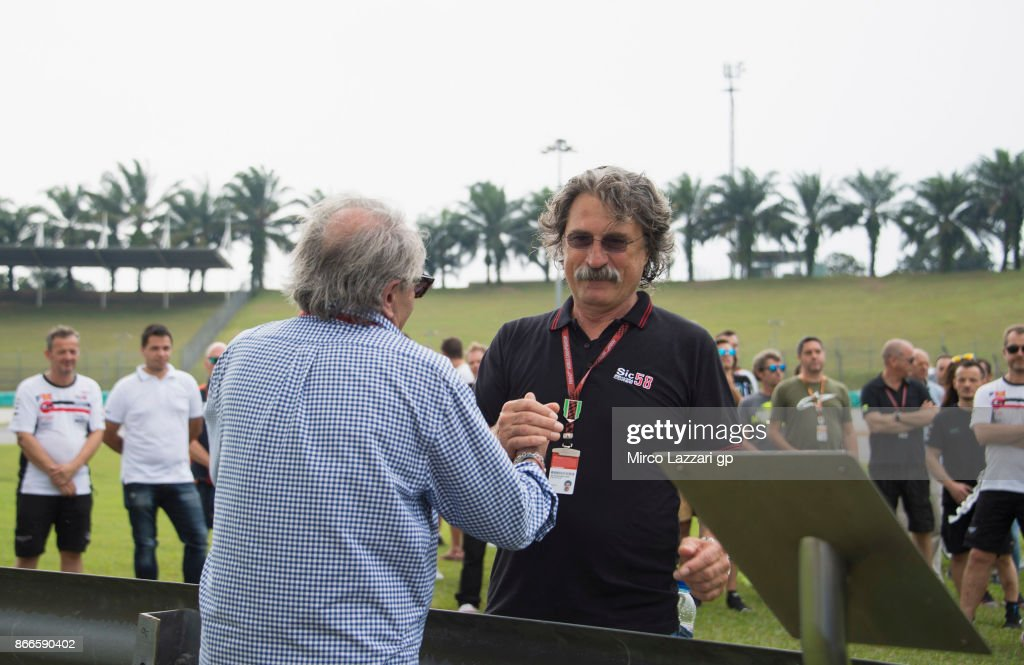 Paolo Simoncelli of Italy (father of Marco Simoncelli) hugs Carlo Pernat of Italy (L) during the 'Track walk to Turn 11 for SIC ' ahead of the MotoGP of Malaysia at Sepang Circuit on October 26, 2017 in Kuala Lumpur, Malaysia.