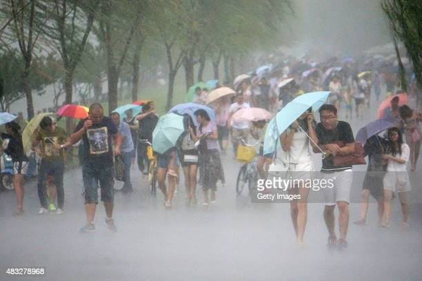 Paople use umbrellas as they walk in strong wind and heavy rain near West Lake as Typhoon 'Soudelor' approaches on August 7 2015 in Hangzhou Zhejiang...