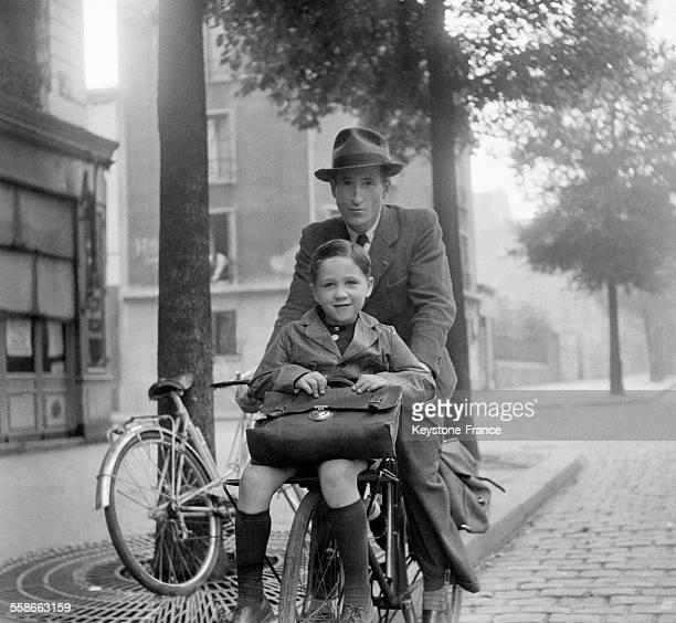 Papa emmenant à l'école son garçon à vélo à Paris France en septembre 1945