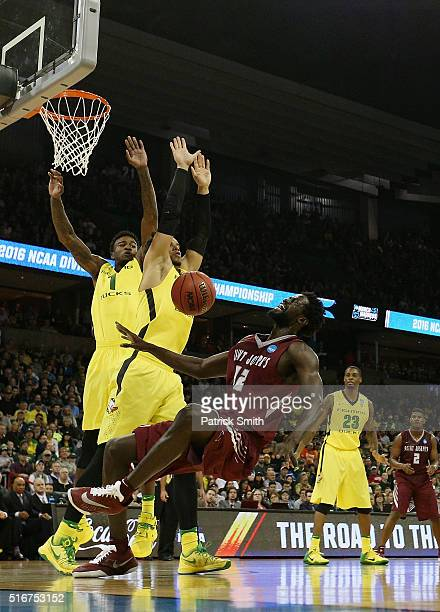 Papa Ndao of the Saint Joseph's Hawks falls as Dillon Brooks and Jordan Bell of the Oregon Ducks defend the net in the first half during the second...