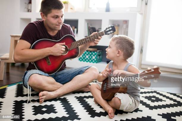 Papa playing guitar for his child