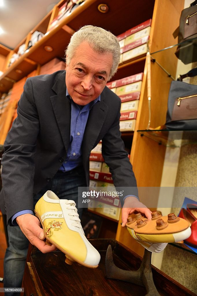 Papal shoemaker Adriano Stefanelli poses with a pair of football shoes with the name of Cardinal Bertone, the number 10 and the Vatican's arms on March 1, 2013 in his shop in Novara. Stefanelli, who made shoes for Popes John Paul II and Pope Benedict XVI, is also expected to have the next Pope as a customer.
