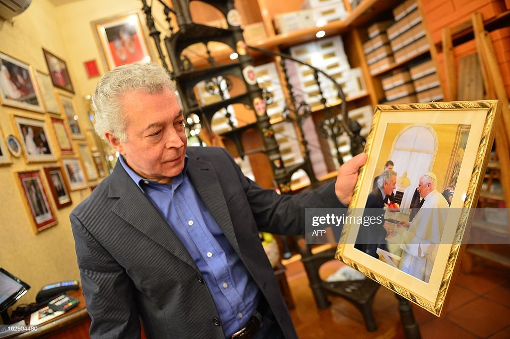 Papal shoemaker Adriano Stefanelli poses with a portrait of him and Pope Benedict XVI on March 1, 2013 in his shop in Novara. Stefanelli, who made shoes for Popes John Paul II and Pope Benedict XVI, is also expected to have the next Pope as a customer.