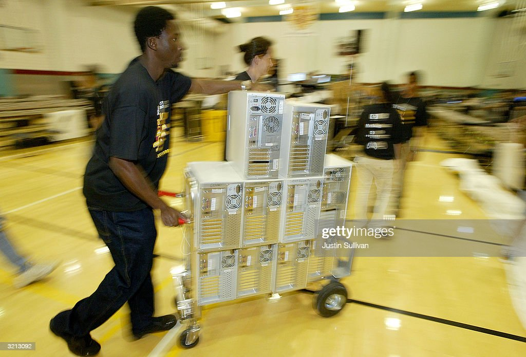 Papanii Okai of San Francisco pushes a cart with desktop computers to be used in Flashmob 1, the first flashmob supercomputer April 3, 2004 at the University of San Francisco in San Francisco, California. Hundreds of computer enthusiasts connected hundreds of computers via high-speed LAN to work together as a single supercomputer in hopes to place in the top 500 fastest supercomputers on earth.