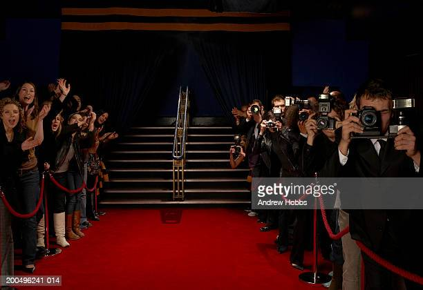 Paparazzi and excited fans greeting celebrity arrivals on red carpet