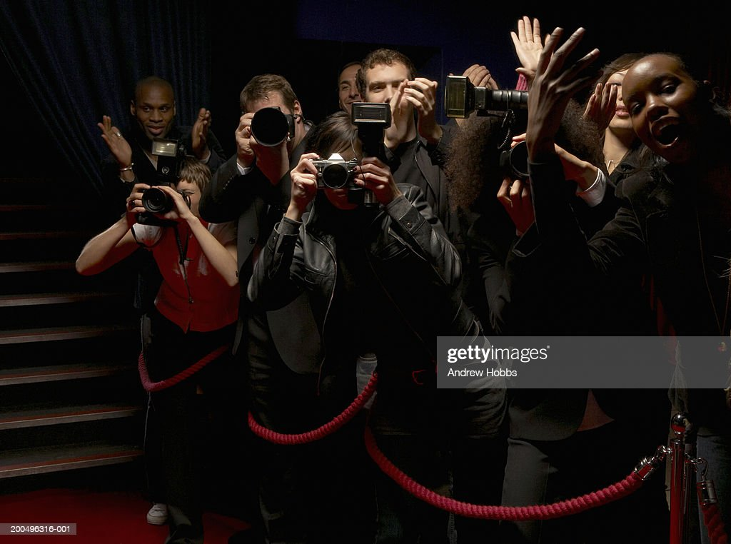 Paparazzi and excited fans standing behind rope barrier on red carpet : Stock Photo