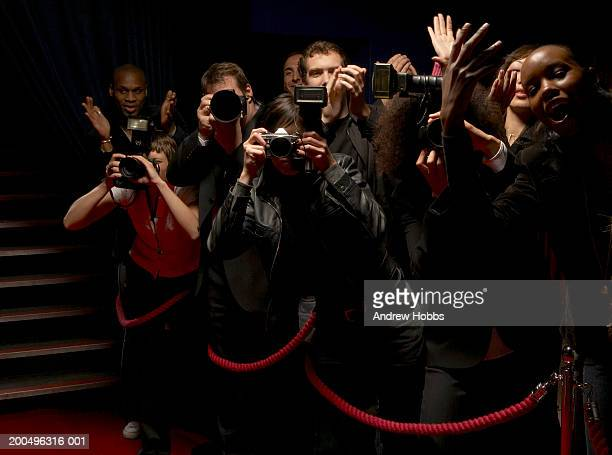 Paparazzi and excited fans standing behind rope barrier on red carpet